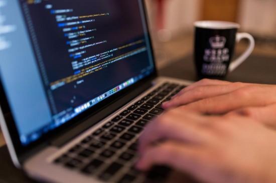 pessoa digitando códigos de programação no laptop