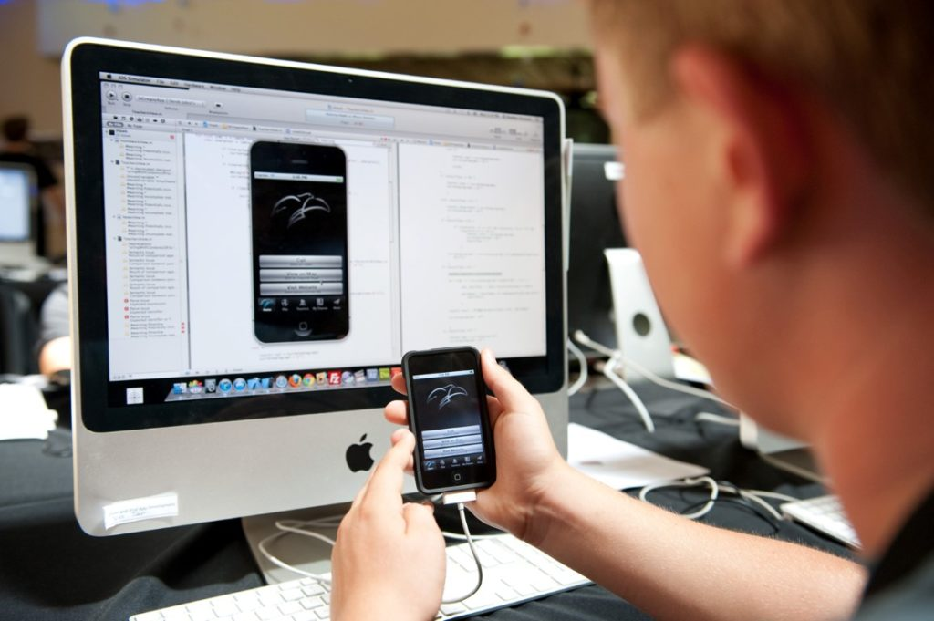 pessoa que trabalha com computador e conecta smartphone